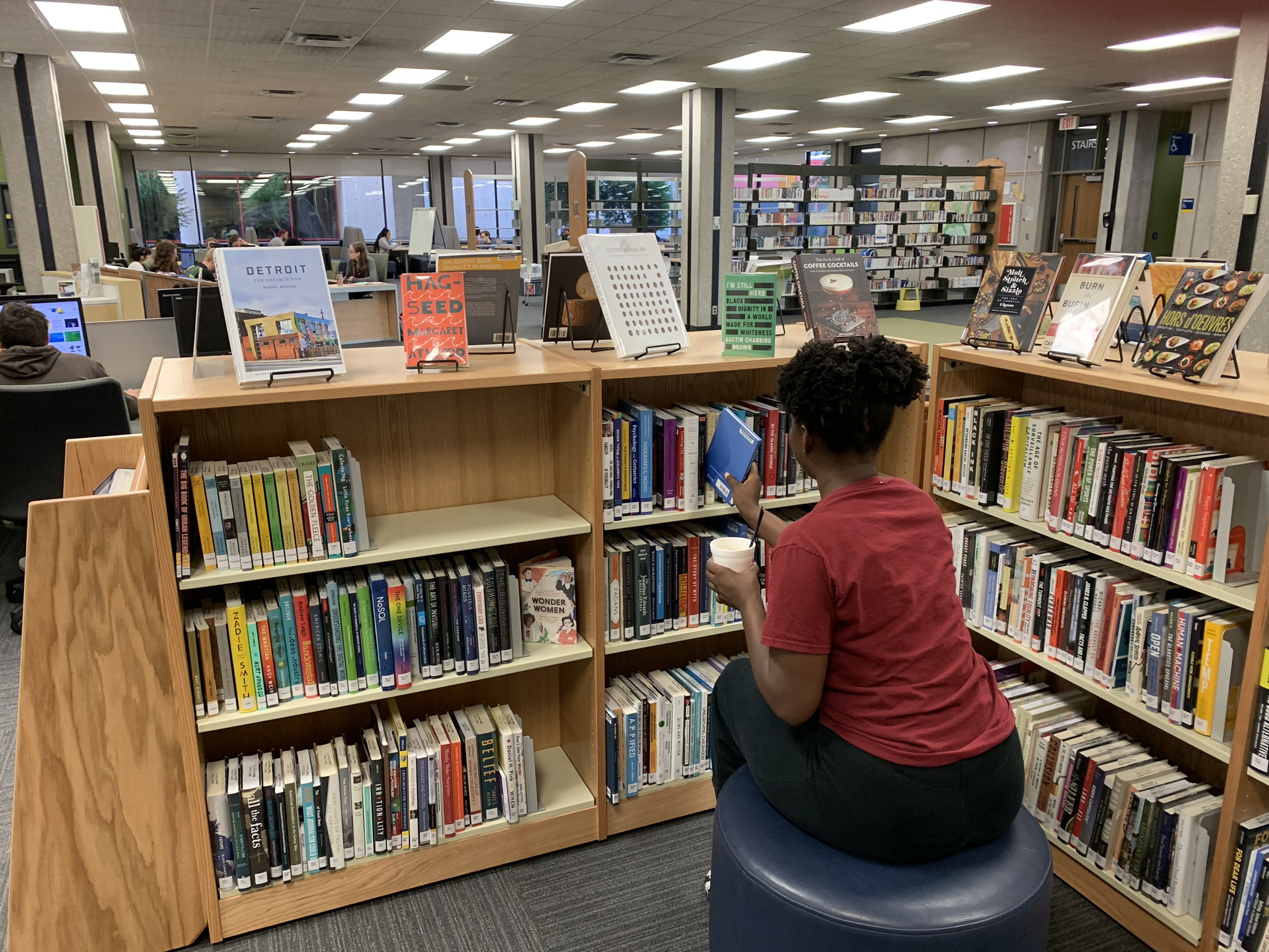 Student enjoying coffee in the New Books area
