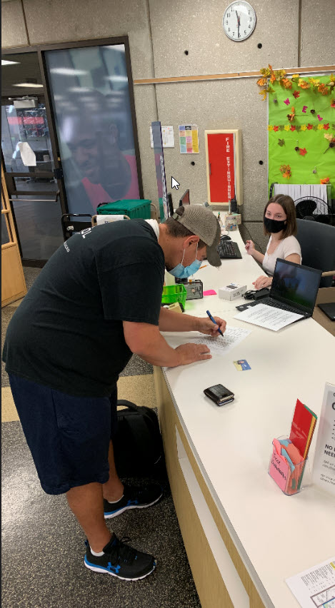 Male student signs paperwork to check out technology at Library Circulation Desk with female student worker assisting.