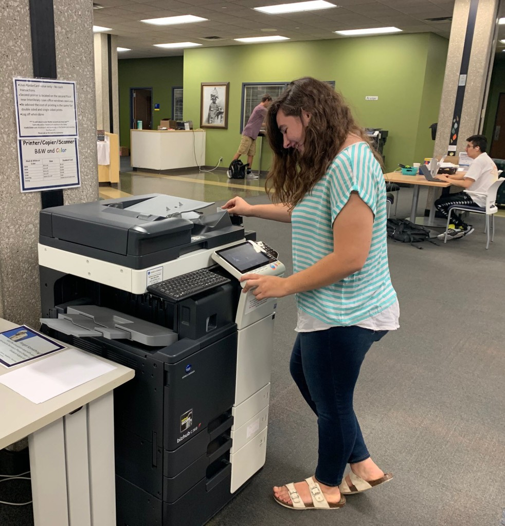 student using printer in the library